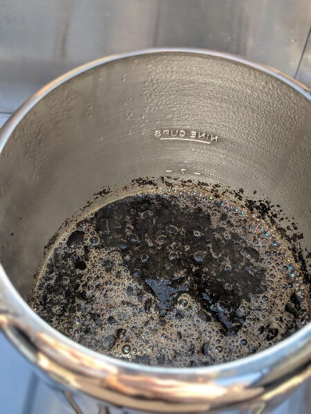 coffee grounds floating in water in stainless percolator to make cowboy camping coffee