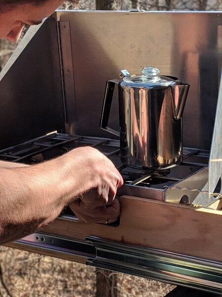 lighting camp stove to make cowboy coffee