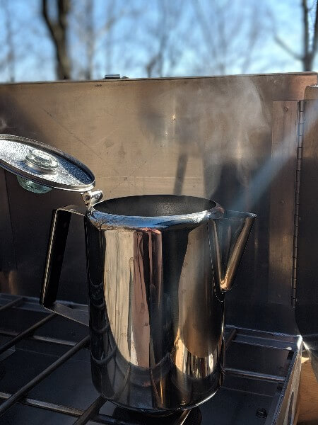 stainless percolator on camp stove to make cowboy camping coffee