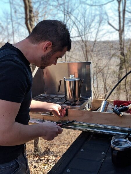 man lighting stove in truck bed kitchen drawer to make camp coffee