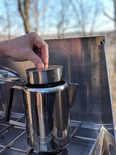 insert percolator apparatus into stainless percolator on camp stove