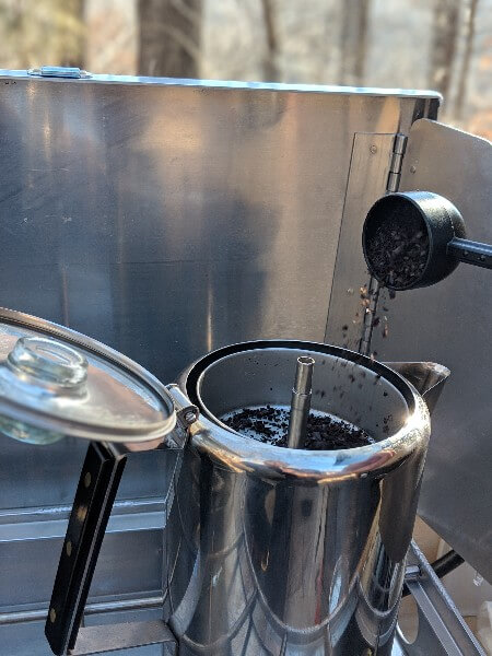 course ground coffee into percolator grounds basket for camping coffee