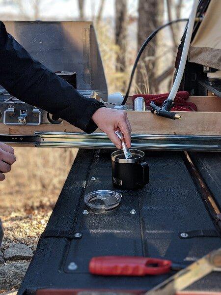 pouring starbucks instant camping coffee into yeti mug