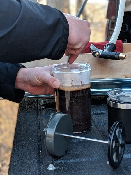 making french press camping coffee on tailgate of truck camper