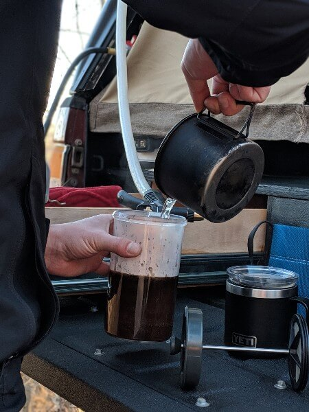 adding hot water to gsi javapress to make french press camping coffee