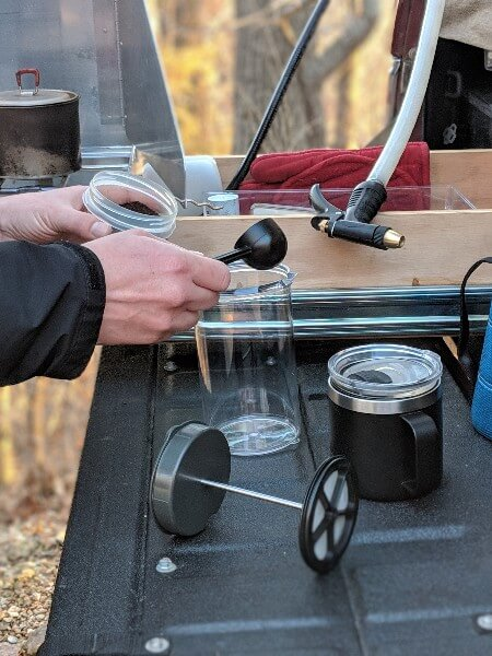 putting coffee grounds into gsi javadrip to make camping coffee