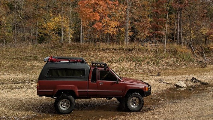 fiberglass topper on maroon toyota pickup shell camper parked by woods