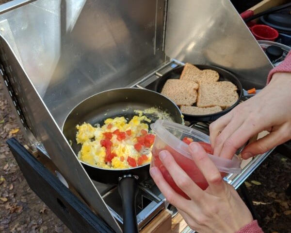 adding presliced tomato to eggs on camping stove for easy camping meals