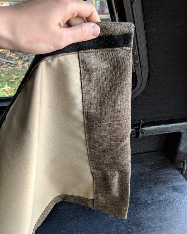 Attach your velcro about 1/2 inch down from the top of the fabric rather than right across the very top. This gives an overall cleaner look  by covering the frame once the curtain is mounted.