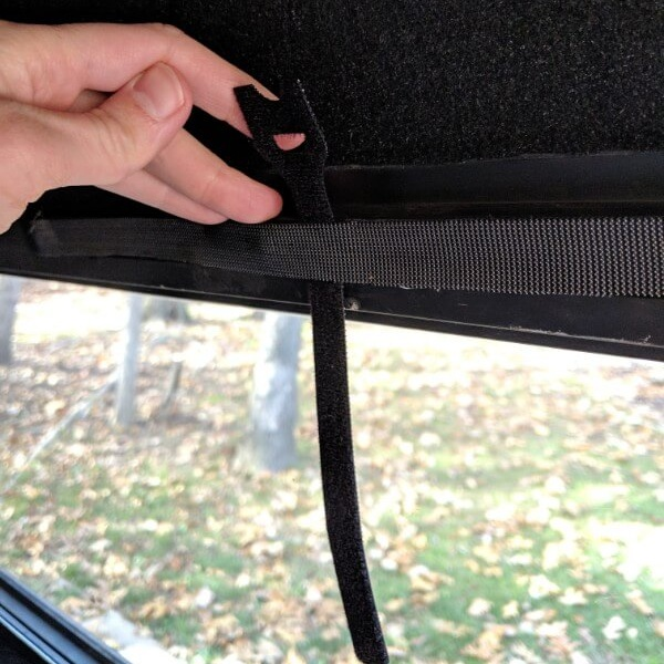 Bundling straps go behind the adhesive velcro. Position them so that only the tab is sticking up - this makes them easy to use when rolling the curtains up.