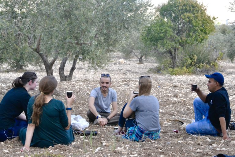 The group relaxing with a cup of tea while taking a break from a hike.