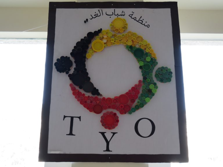 Plastic bottle caps of different shapes and colors create the TYO logo.
