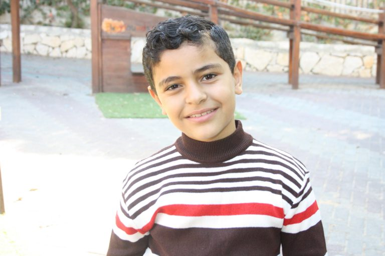 Salim, a student in the academic support program, is all smiles on the playground at TYO.