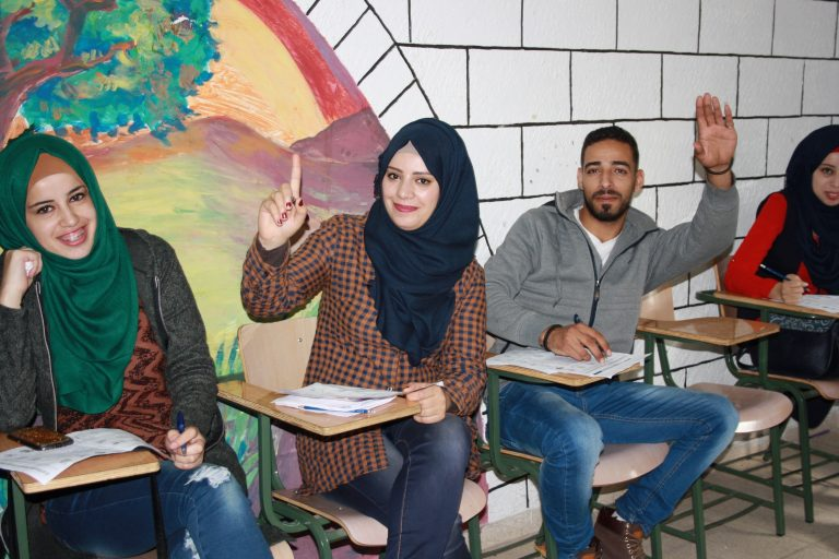 Students of the STEP! II EFL program smile as they prepare to answer a question.
