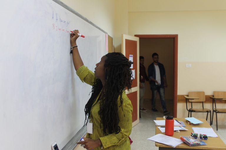 EFL Fellow Mecca writes on the board as students enter the classroom in the first week of EFL class.