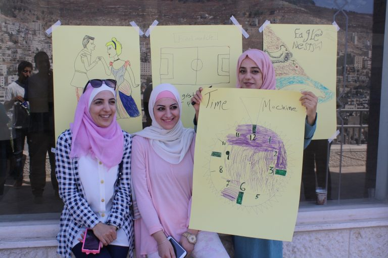 Three EFL students show their movie posters created after discussing film vocabulary during Pop Culture week.
