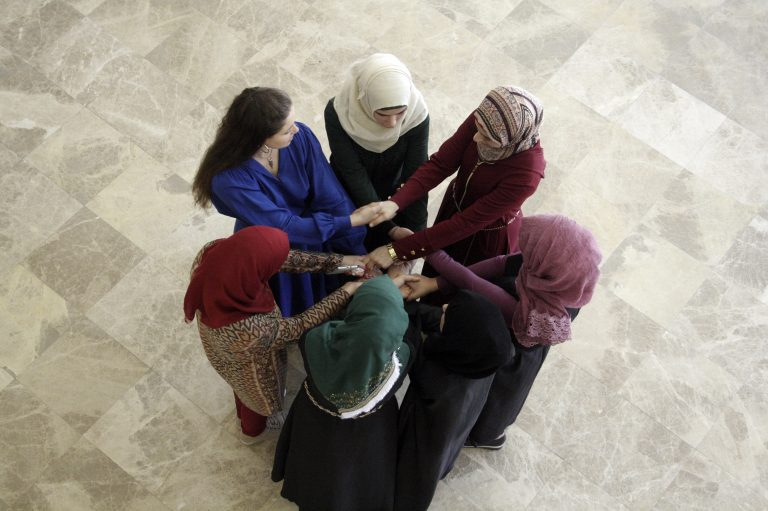 An EFL class plays a game with their teacher on the first day of class.