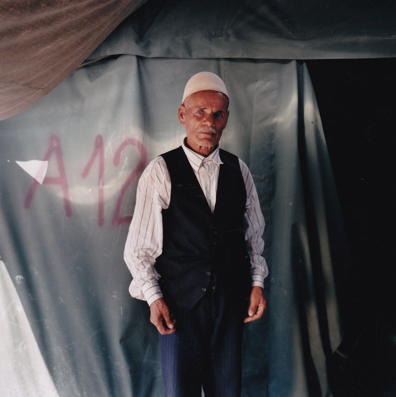 "Ramadan, age 73 Neprosteno camp, Macedonia, June 10 1999. ""I kept my hat from Kosova, and I will never let anyone take it from me. The Serbian police used to say, 'what do you need this hat for?' I didn't let them take it. It's our traditional Albanian hat and the Serbs don't like it. They would order me, 'Take off your hat.' They wanted to throw it in the fields. I was hit by the Serbian police four or five times because of my hat. They can kill me, but I won't take my hat off. I sit all day and long for my village. All I want is to go back to Kosova. It's all I want. I want to be there."""