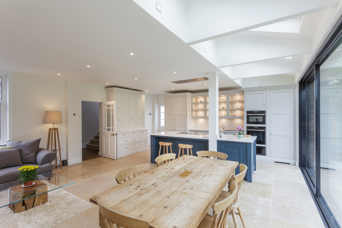 white and navy bespoke kitchen with natural wood furniture