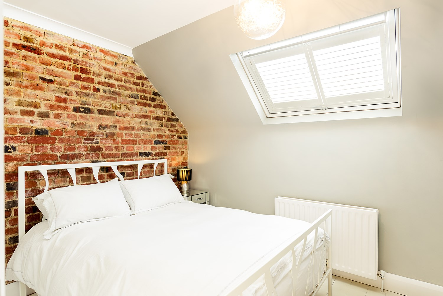 exposed brick wall in loft bedroom with skylight