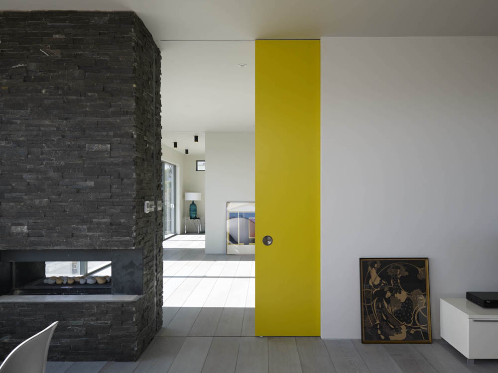 large two sided stone chimney with yellow pocket door in white contemporary home