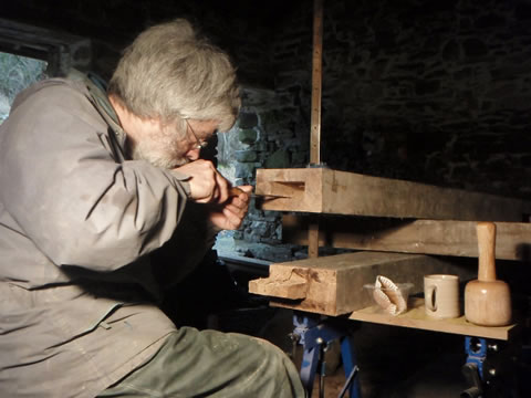 man working with wood for timber frame stone barn conversion