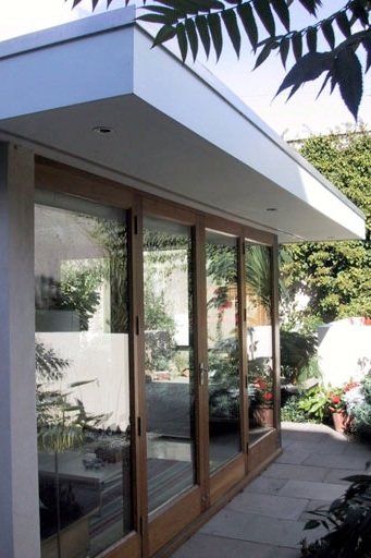 contemporary garden room with glazed doors and roof overhangs with lighting in soffit