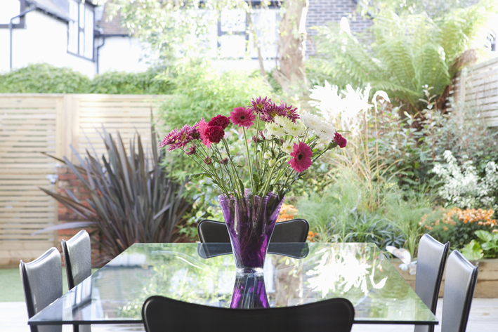 dining table with flowers and lush landscaping in garden beyond