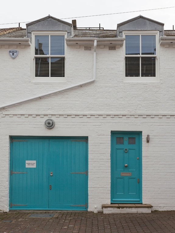 white mews house exterior with turquoise doors