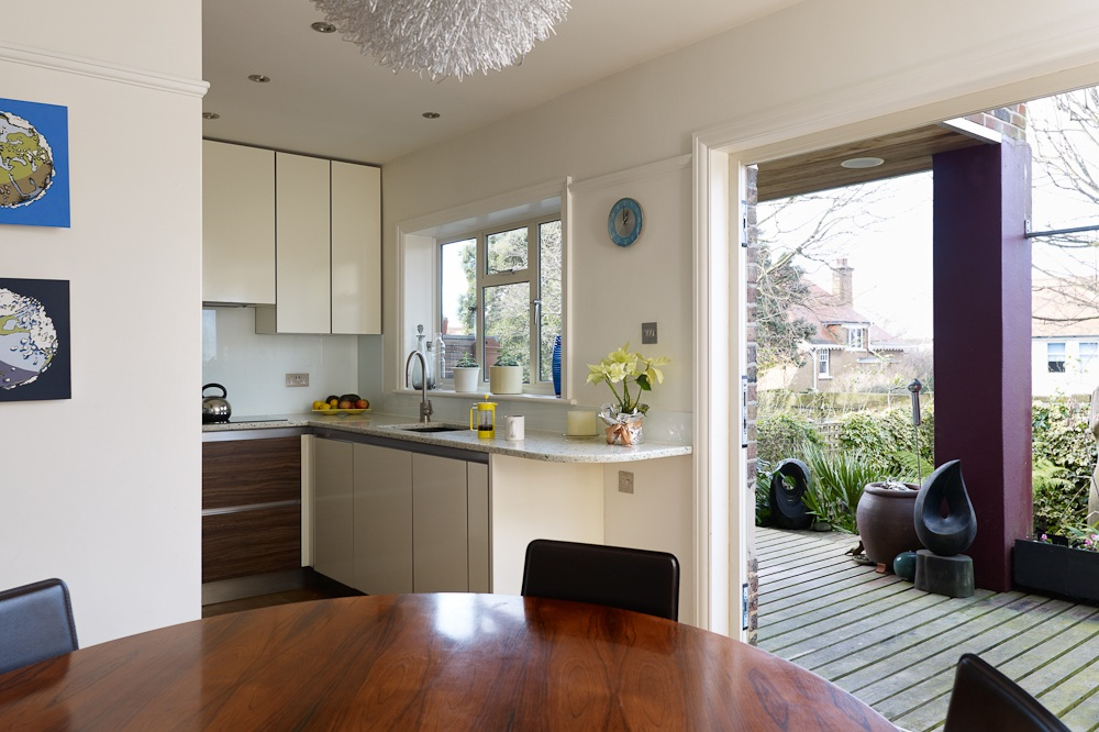 kitchen dining area spilling into deck and lush landscaped garden