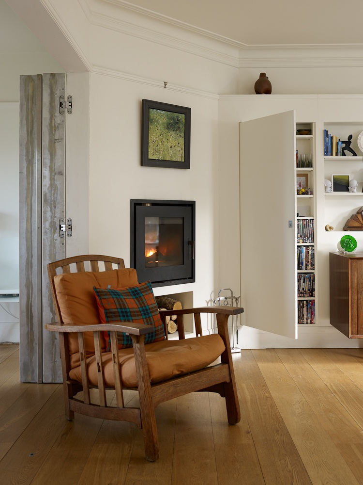 cosy armchair beside living room wood stove