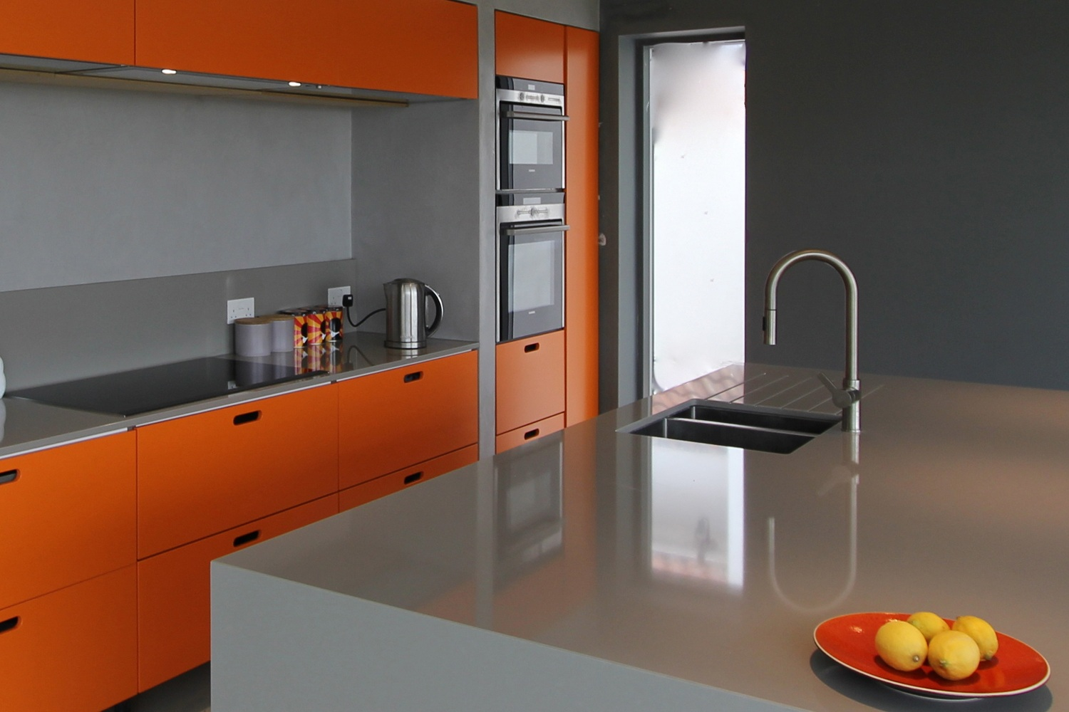 orange accented modern kitchen with lemons on a red plate