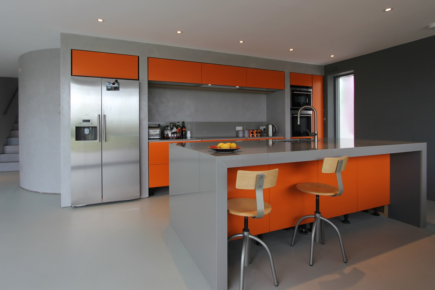 orange accented modern kitchen with island and two stools