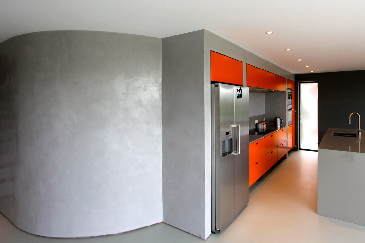 curved grey wall with orange accented modern kitchen