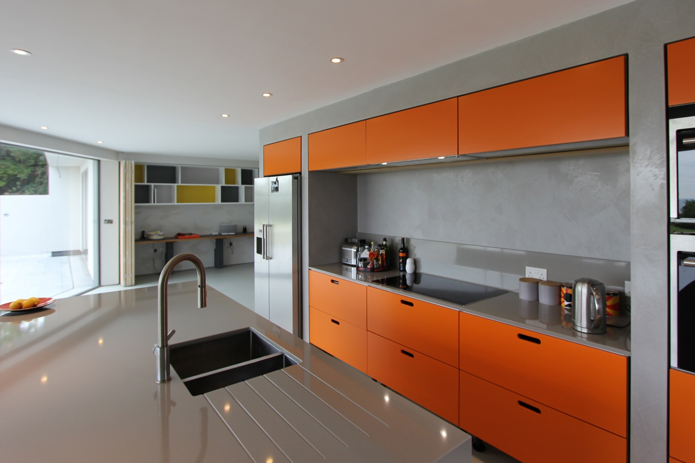orange accented modern kitchen with large glazing beyond