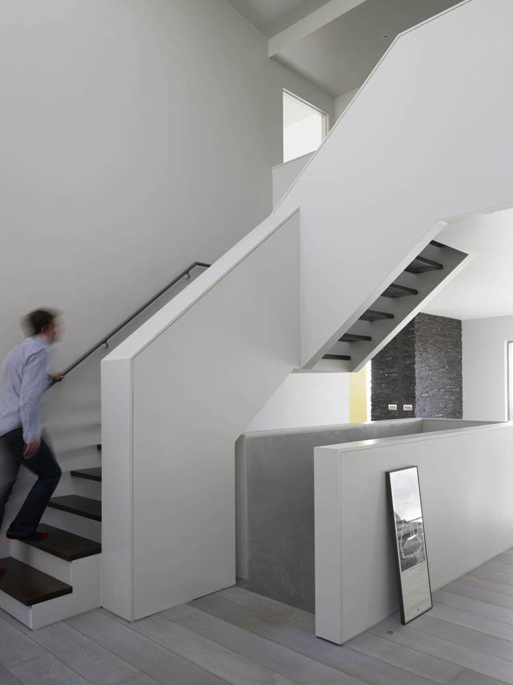 contemporary minimalist and sculptural white stair in double height space