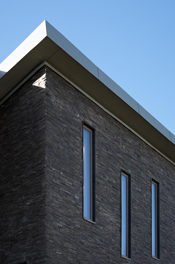 slate cladding corner details with rhythmical windows and blue sky