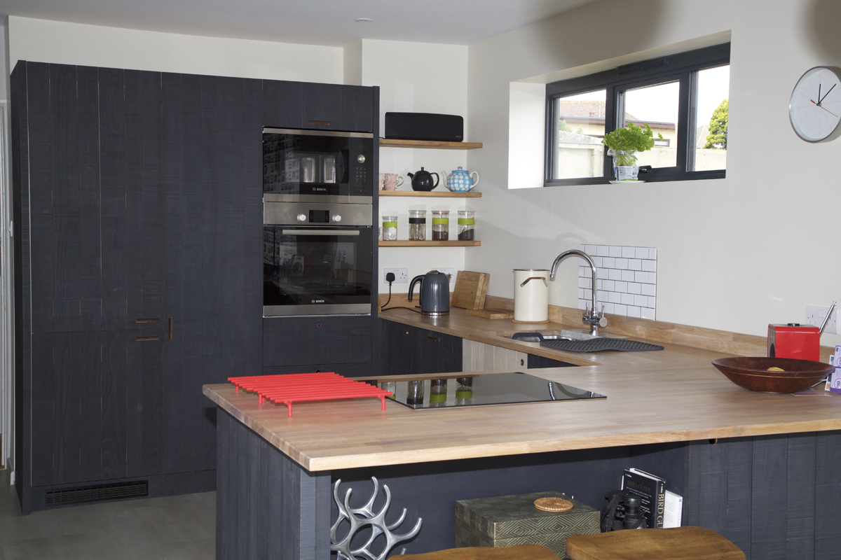 bespoke kitchen with dark cabinets and wood countertops