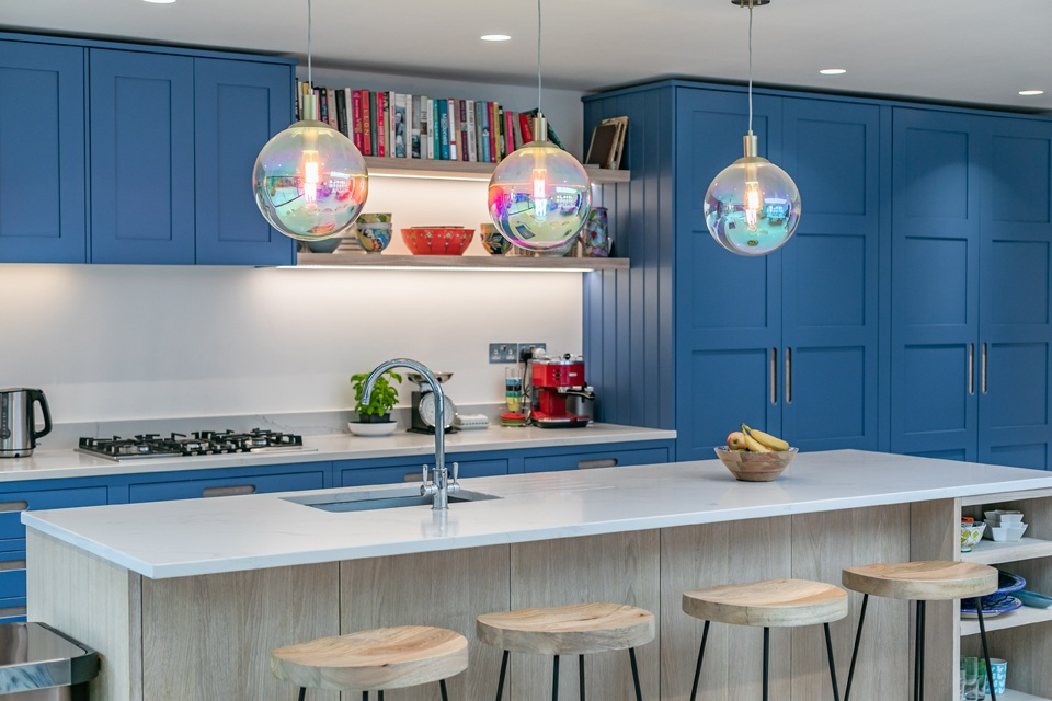 bold blue kitchen with glass ball pendants