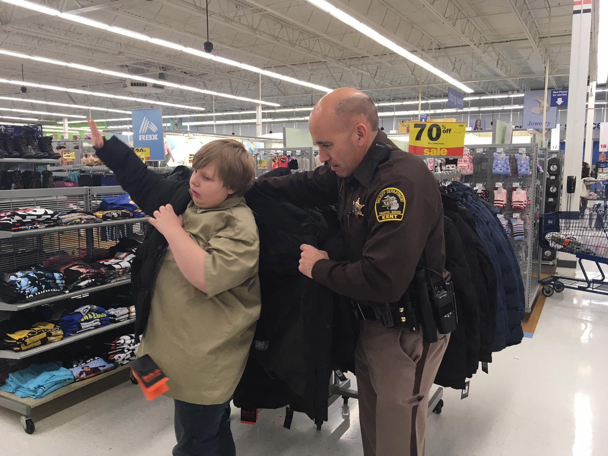 Deputy John Shumay helps Sylas Holbrook pick a warm coat.