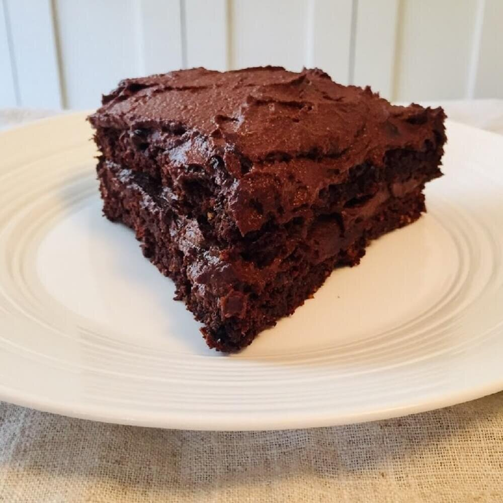 vegan gluten free chocolate cake slice on a white plate with a linen tablecloth underneath.