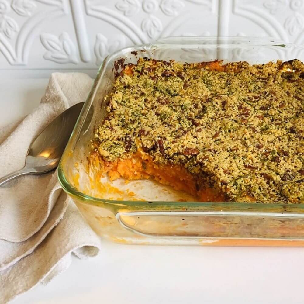 vegan sweet potato casserole in a glass dish next to a spoon and cloth napkin.