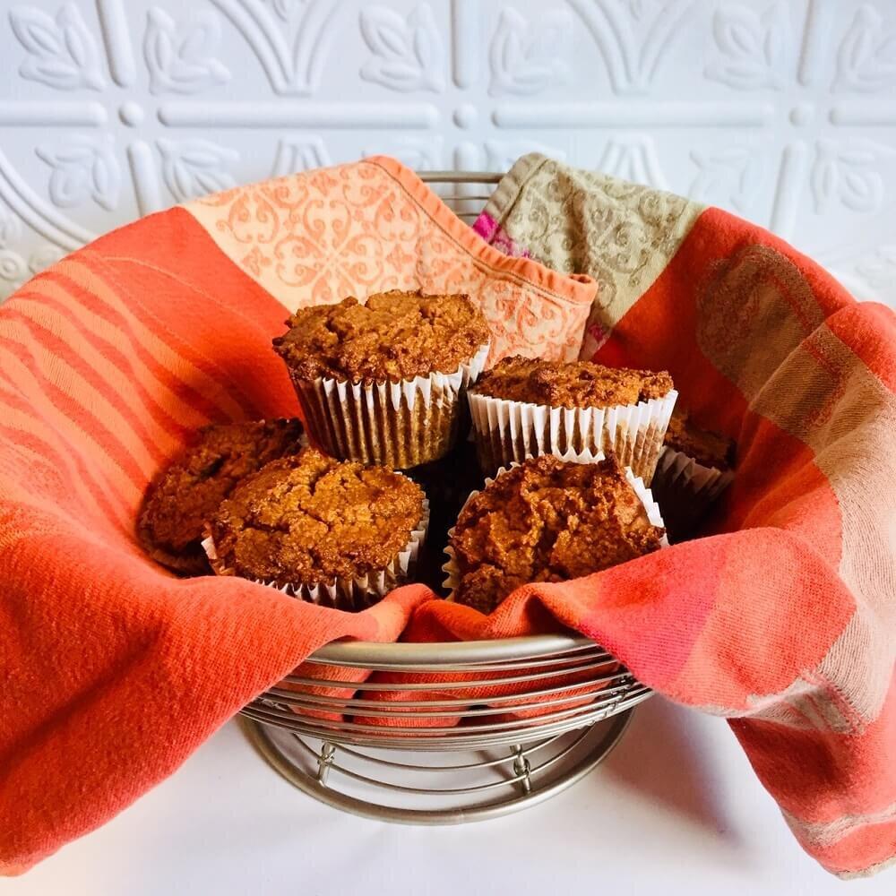 paleo pumpkin muffins in a wire mesh bowl with an orange tea towel.