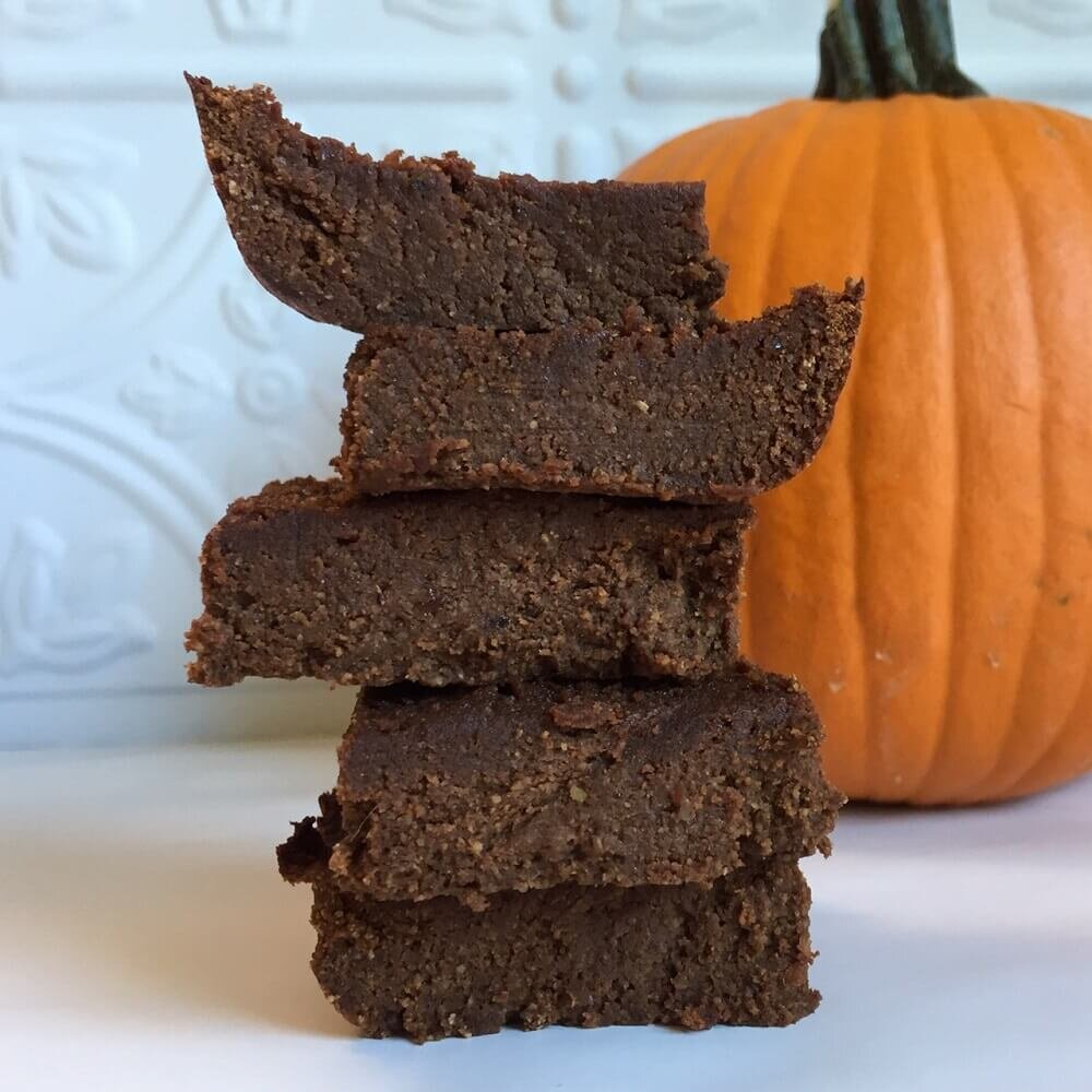 vegan pumpkin brownies stacked with a pumpkin in the background