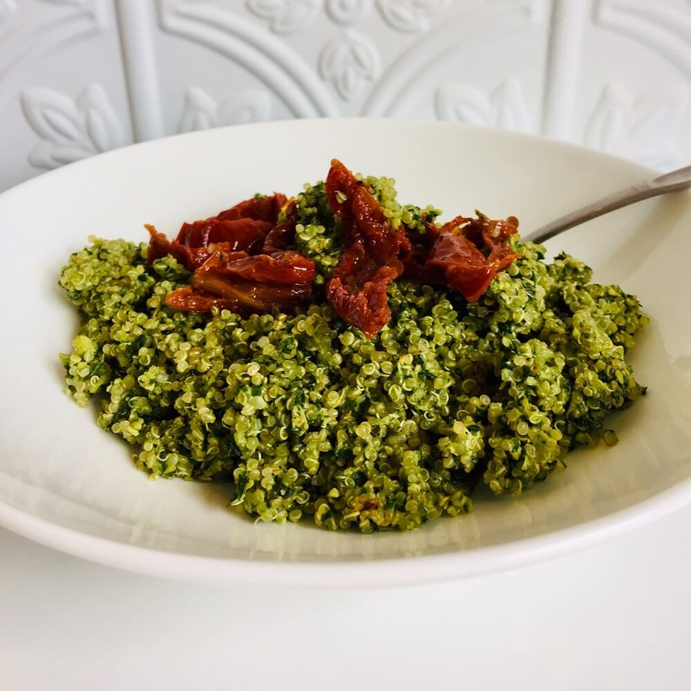 pesto quinoa in a bowl with sun dried tomatoes on top