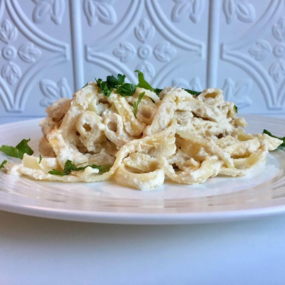 vegan alfredo sauce on fettucine noodles garnished with fresh parsley.