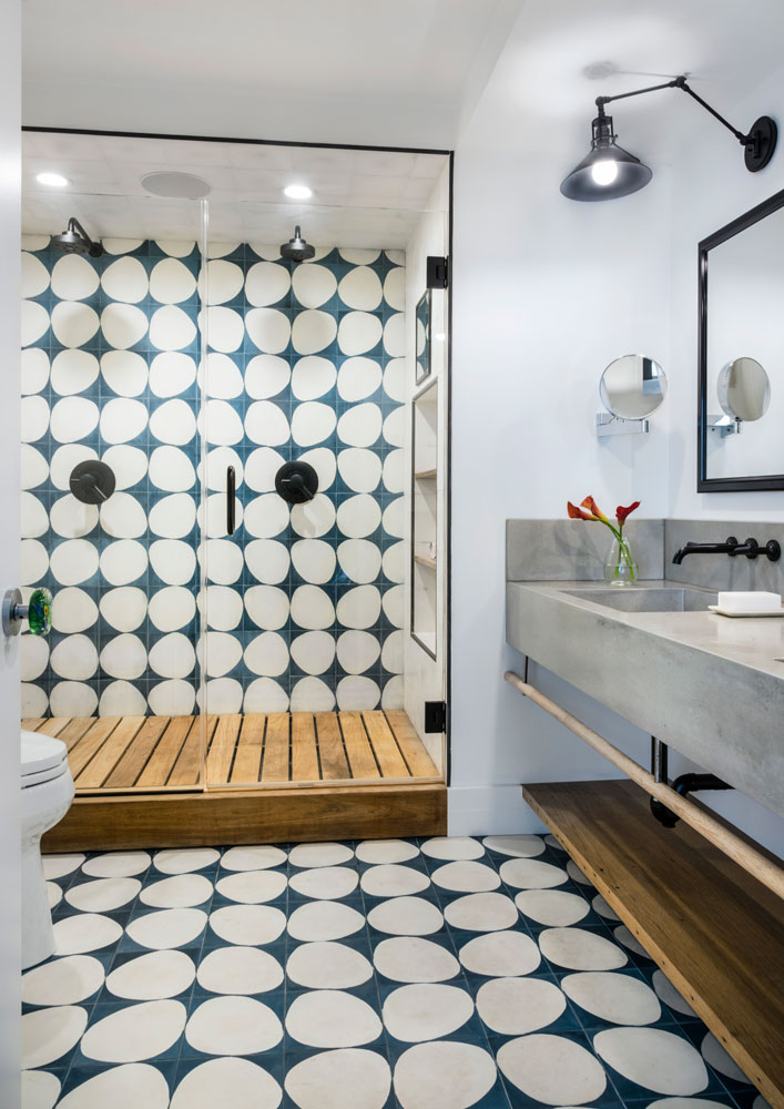 - We really appreciate how the bathroom came out with these uniquely shaped tiles, not only for the appearance but also because this part ended up taking a lot of time. We pushed for the blue grout to fill in between the tiles because it looks great, but we didn't realize at the time that it would end up staining part of the white tiles. Take the lesson from us, porous tiles will stain next to certain colored grouts. We ended up spending over 18 hours just scrubbing and cleaning the tile, but was well worth it to provide such a clean aesthetic!