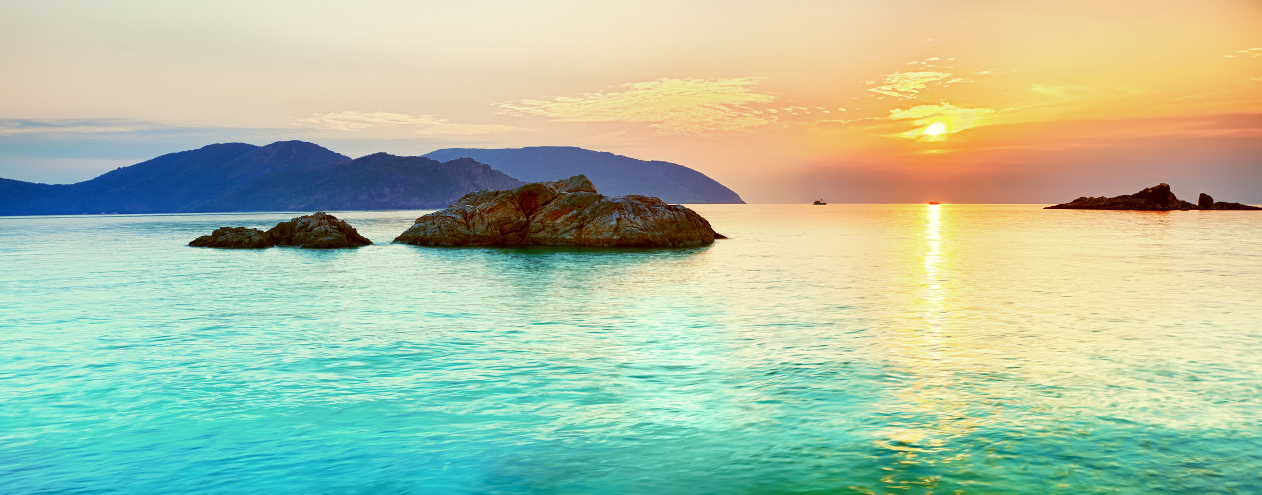 turquoise ocean sunset and mountains.jpg