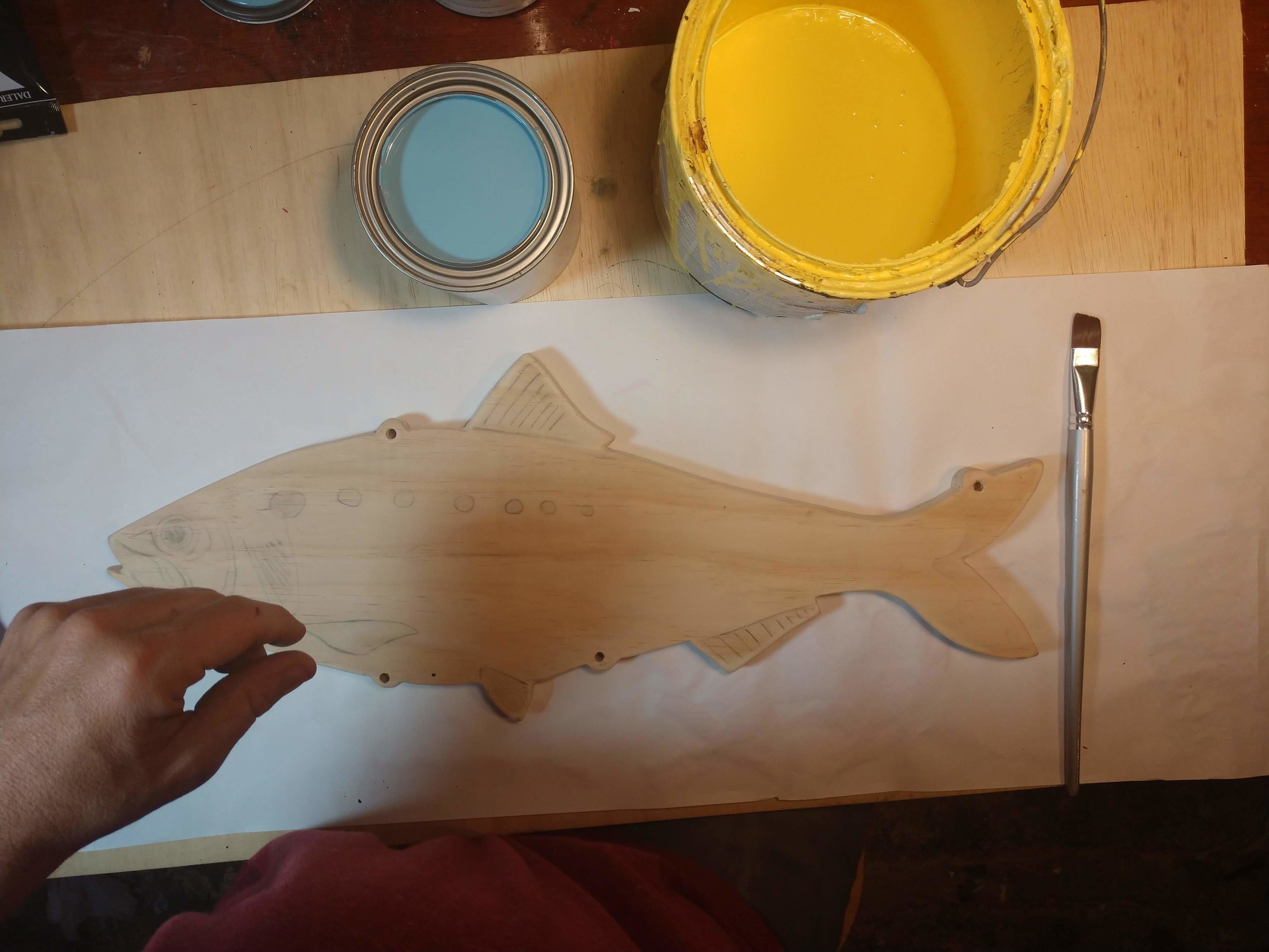 Here is a freshly cut wooden fish getting ready for a coat of paint. Look at the holes and you'll notice the syleized bumpouts.