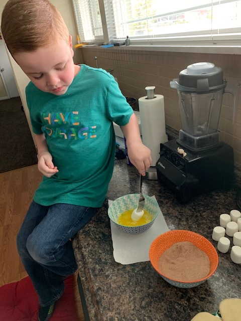 The fun part. You can totally use your hands but my son likes to use a fork. In with the butter, and then the cinnamon sugar mix.